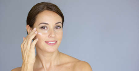 Photo for Beautiful young woman applying face cream to her cheek bone in a beauty  skincare or cosmetics concept  on grey with copy space - Royalty Free Image