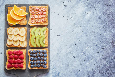 Foto de Six Healthy breakfast toasts. Wholegrain bread slices with peanut butter and various fruits. Served on grey cutting board. Top view, grey stone background. Dieting concept with cpoy space - Imagen libre de derechos