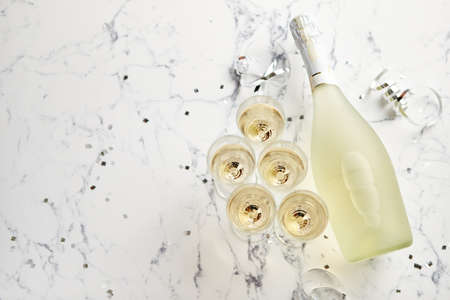 Foto de Champagne glasses and bottle placed on white marble background. Party and holiday celebration concept with confetti and serpentines. With copy space. - Imagen libre de derechos