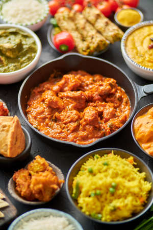 Photo pour Various Indian dishes on a table. Spicy chicken Tikka Masala in iron pan. Served with rice, naan and spices. Set of different kind Indian food. - image libre de droit