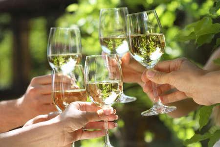 Photo pour Celebration. People holding glasses of white wine making a toast. Shallow DOF. - image libre de droit