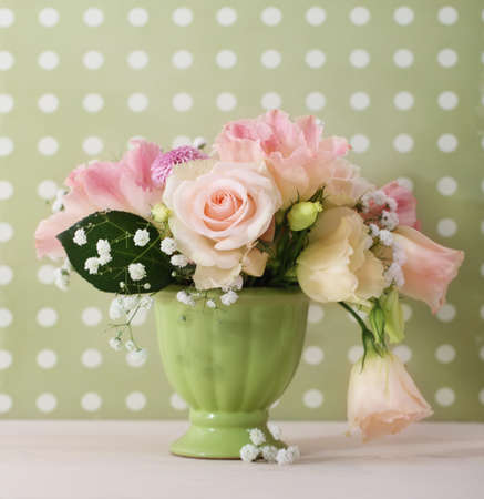Bouquet of white and pink roses in the green vase