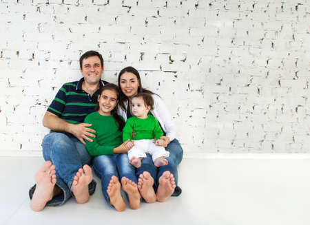 Photo pour Portrait of a happy smiling family near white brick wall - image libre de droit