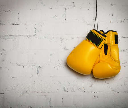 Pair of yellow boxing gloves hanging on a brick wall