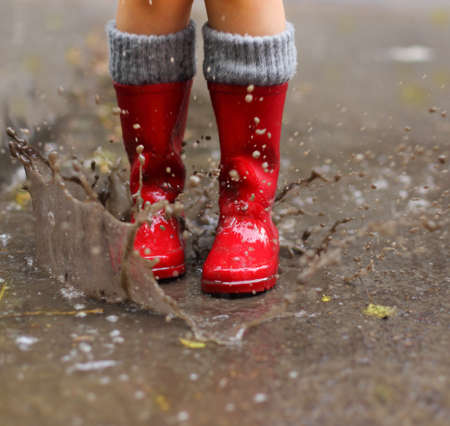 Child wearing red rain boots jumping into a puddle. Close upの写真素材