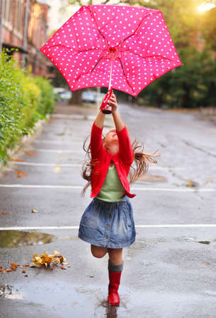 Child with polka dots umbrella wearing red rain boots jumping into a puddleの写真素材