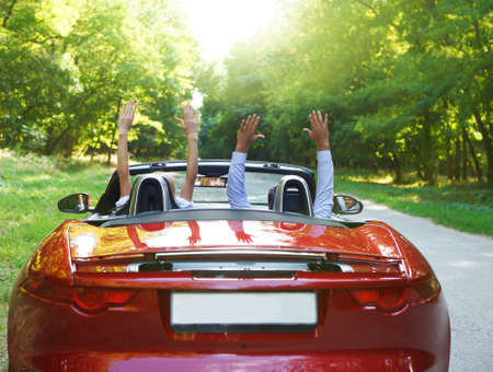 Happy free couple driving in red retro car cheering joyful with arms raised. Road trip travel concept