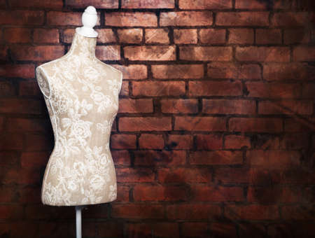 Antique dress form with vintage look against brick