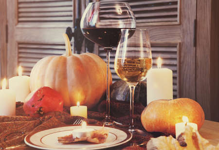 Autumn place setting. Thanksgiving dinner. Fall season fruit, pumpkins, plates, wine and candles. Thanksgiving dinnerの写真素材