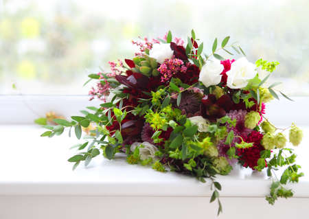 Unusual wedding composition with succulent flowers, fig and hop in retro style near the window