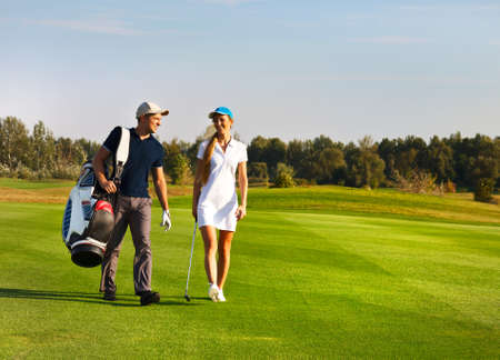 Young sportive couple playing golf on a golf course walking to the next hole