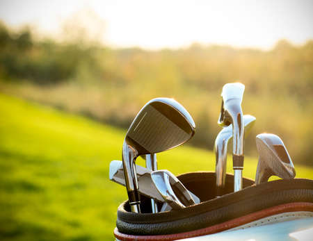 Foto de Golf clubs drivers over green field background. Summer sunset - Imagen libre de derechos