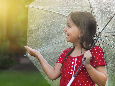 Little girl wearing polka dots dress under umbrella in rainy dayの写真素材