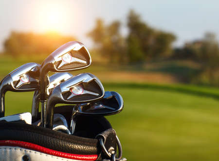 Photo for Golf clubs drivers over green field background. Summer sunset - Royalty Free Image