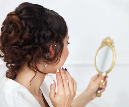 Gentle young bride looks in the mirror. Bridal morning