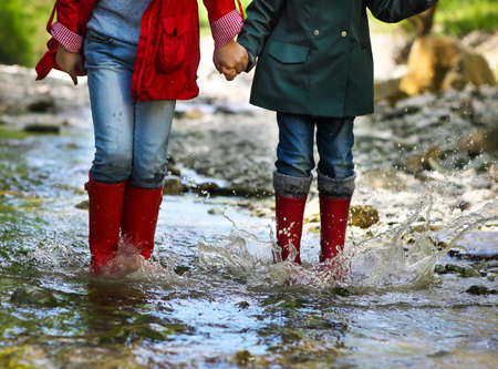 Children wearing rain boots jumping into a mountain river. Close up