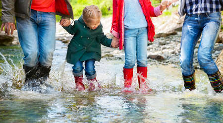 Happy family with two children wearing rain boots jumping into a mountain riverの写真素材