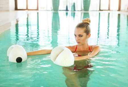 Blond young woman doing aqua aerobics with foam dumbbells in swimming pool at the leisure centre