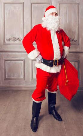 Photo of happy Santa Claus with big bag of presents looking at camera