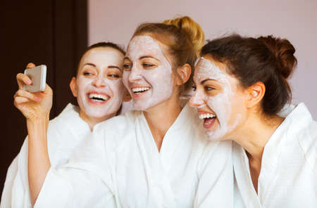 Photo pour Three young happy women with face masks taking selfi at spa resort. Frenship and wellbeing concept - image libre de droit