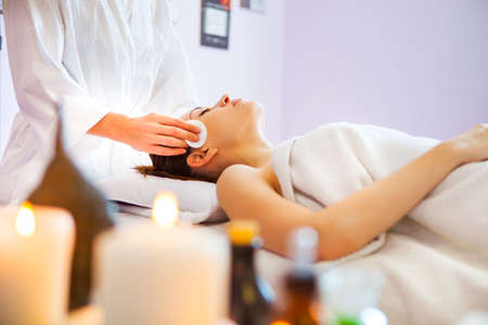 Relaxed woman with a deep cleansing nourishing face mask applied to her face. Spa treatmentの写真素材