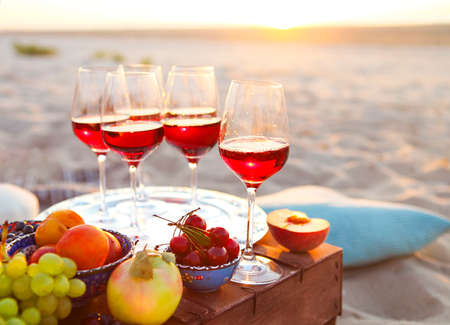 Glasses of the red wine on the sunset beach picnic