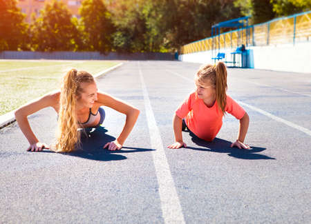 Photo for Mother and little daughter are doing exercise in the stadium. Family doing fitness at the stadium. Healthy family concept - Royalty Free Image