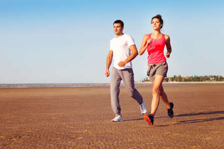 Photo pour Portrait of couple jogging outside, runners training outdoors working out in nature against blue sky - image libre de droit