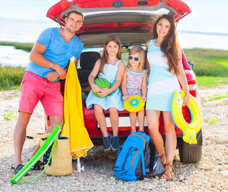 Portrait of a smiling family with two children at beach by car