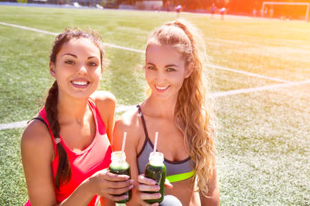 Photo pour Two happy women drinking vegetable smoothie after fitness running workout on stadium. Fitness and healthy lifestyle concept - image libre de droit