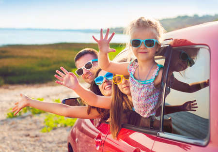 Photo pour Portrait of a smiling family with two children at beach in the car.  Holiday and travel concept - image libre de droit