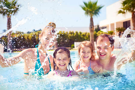Photo pour Happy family with two kids having fun in the swimming pool. Summer vacation concept - image libre de droit