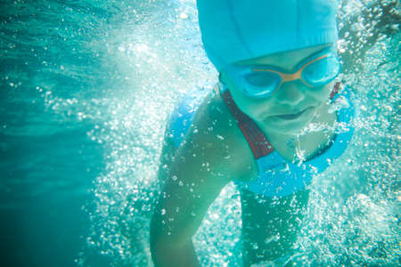 Photo pour Little girl in a bathing suit swims in the pool underwater - image libre de droit