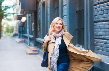 Photo pour Middle age woman goes through the city and smiles. Happiness concept. - image libre de droit