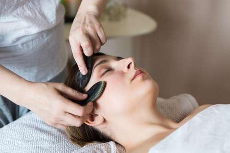 Photo pour Young woman have face guasha treatment at asian beauty clinic - image libre de droit