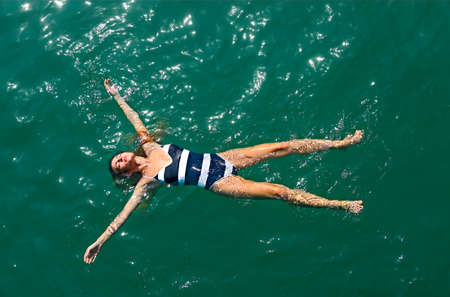 Aerial top down view of a girl in a white and blue swimsuit in the sea