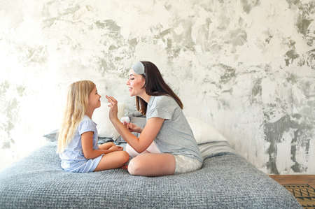 Photo for Cute smiling mother and daughter applying face cream together  - Royalty Free Image