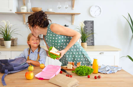 Photo pour Beautiful brunette mother and her daughter packing healthy lunch and preparing school bag in the kitchen - image libre de droit