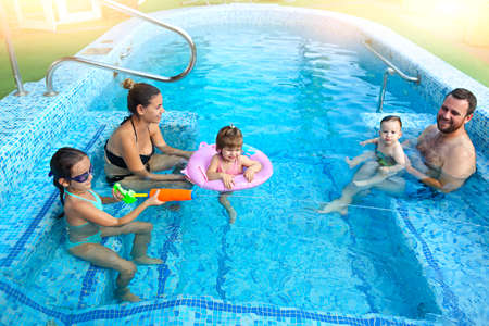 Photo for Happy young family with little kids having fun together in the pool - Royalty Free Image