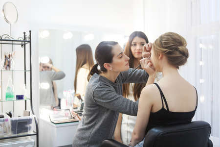 Foto per Makeup teacher with her student girl. Make up tutorial lesson at beauty school. Make up artist work in her studio. Portrait of visagist applying makeup on the eyebrow. Master class - Immagine Royalty Free