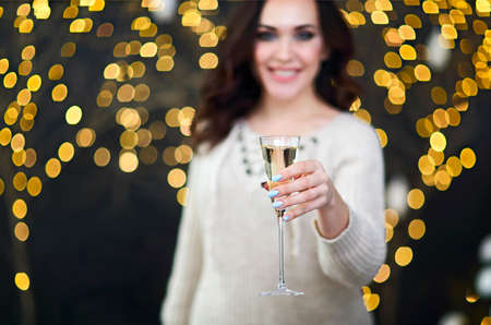 Foto de Smiling woman in the sweater with glass of champagne over lights background. Party, drinks, holidays, luxury, friendship and celebration concept - Imagen libre de derechos