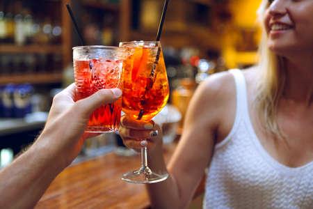 Foto de Woman and man raising a glasses of coktails in the bar background - Imagen libre de derechos