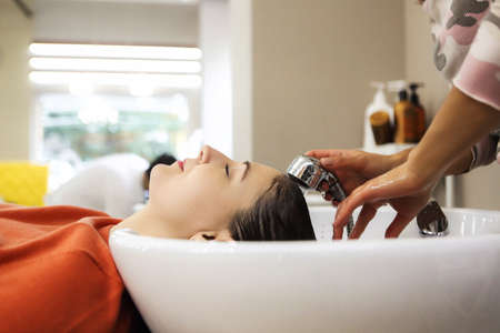 Photo pour Cheerful young woman enjoying head massage while getting her hair washed by a professional hairdresser.  Beauty care, hairstyling, fashion, lifestyle glamour concept - image libre de droit