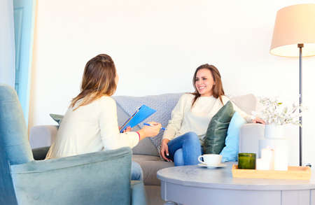 Photo pour Woman in armchair with notes consulting smiling young woman on couch having therapy session - image libre de droit