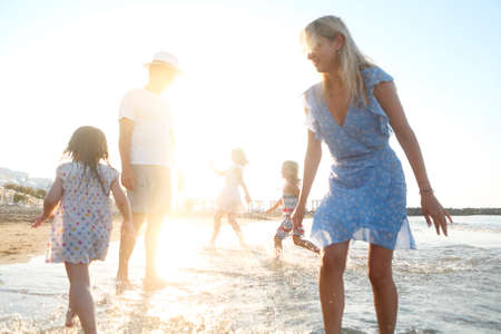 Photo pour Cheerful young mother and father with little daughters walking in clean sea water and having fun together during sunset in nature - image libre de droit