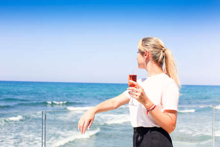Photo pour Side view of relaxed young female in casual wear holding glass of rose champagne and enjoying fresh breeze while standing aboard of ship during sea trip - image libre de droit