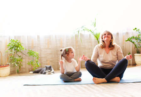Foto de Mature woman and little girl sitting on mat in lotus pose and meditating while doing yoga in spacious room at home together - Imagen libre de derechos