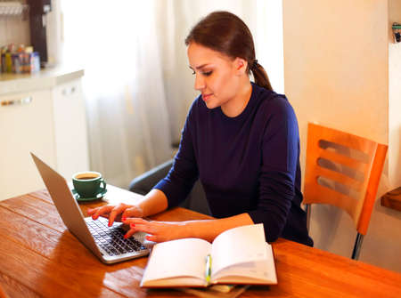 Foto de Youg female freelancer typing on laptop while working remotely from home at wooden table with books - Imagen libre de derechos