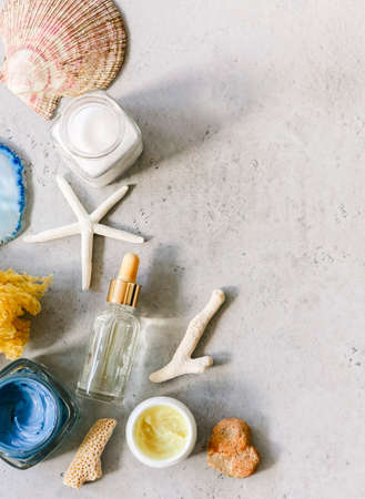 Top view of various cosmetic products in jars arranged on table with seashells and mineral stoneの写真素材