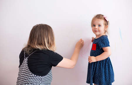 Photo pour Side view of woman scolding little girl for painting walls in modern apartment - image libre de droit